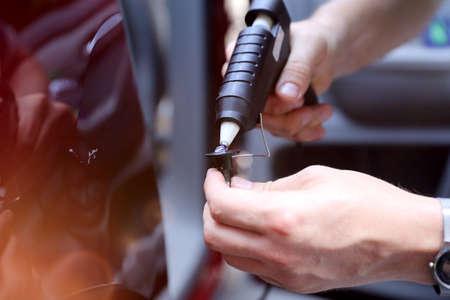 Man fixing car dent by himself