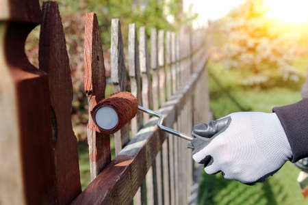 Painting wooden fence with brown paint outside