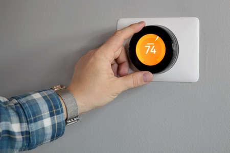 Man is Adjusting a  temperature  in modern living room 版權商用圖片