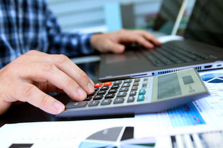 Businessman / accountant is doing calculations. Tax return.