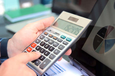 Businessman / accountant is doing calculations. Tax season.