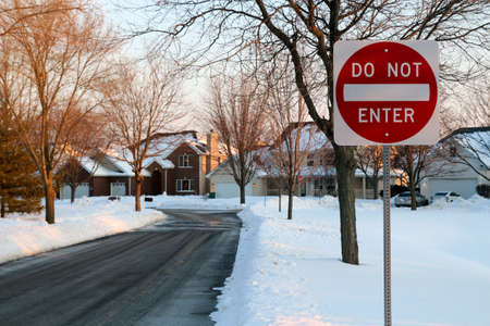 Do not enter sign on the residential building background, entry is prohibited. Winter, snowfall in North American suburban. Icey, snowy street