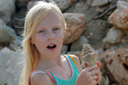 Young blonde girl surprised and holding a seashell