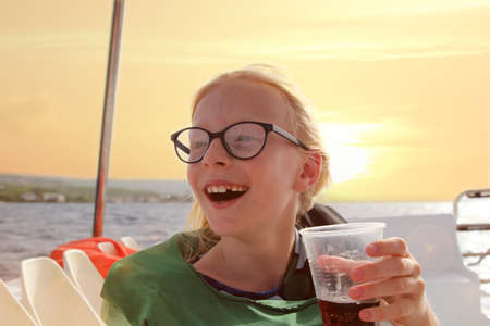 Young blonde girl in glasses have fun discovering islands on summer coastal cruise. Travel adventure, yachting with kids on family vacation. 版權商用圖片