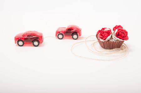 pull toy: dos coches de juguete de color rojo est�n llevando unas rosas