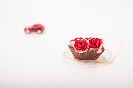 pull toy: un coche de juguete de color rojo está llevando a algunas rosas