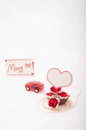 pull toy: un coche de juguete de color rojo est� llevando a algunas rosas con una tarjeta diciendo C�sate conmigo! Foto de archivo
