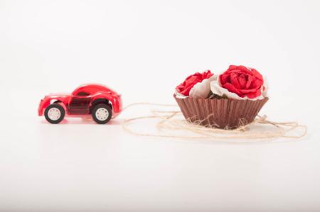 pull toy: un coche de juguete de color rojo est� llevando a algunas rosas