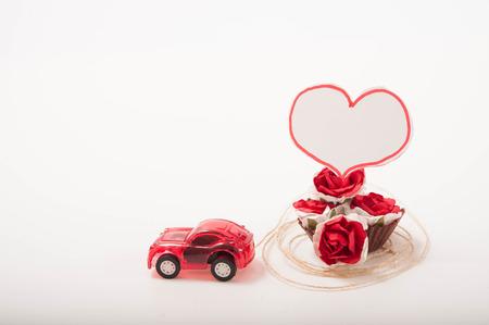 pull toy: un coche de juguete de color rojo con rosas y una tarjeta en forma de corazón