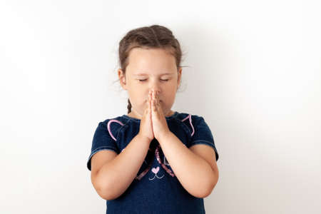 A girl in a blue denim dress clasps her hands in front of her face, closes her eyes, and prays