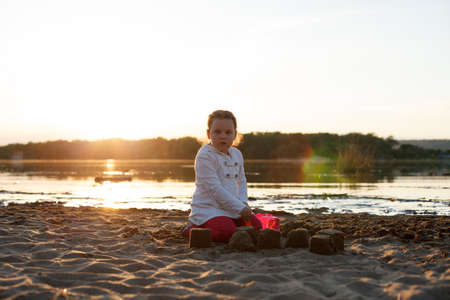 a girl plays with sand on a sandy beach on the river Bank during sunset.