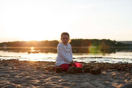 一个女孩在日落期间,在河岸的一个沙滩上的沙子。