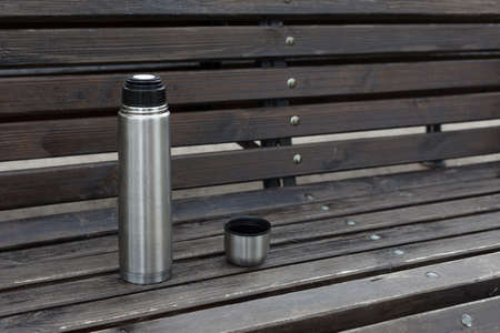 open steel metal thermos with tea or coffee on a wooden bench.