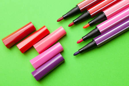 five open markers or pens of pink, purple, pink color lie like steps on a green background, isolated mock up