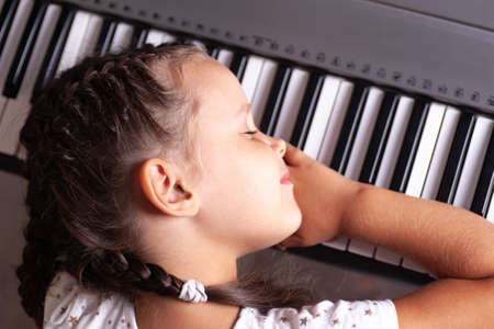 baby girl in white dress sleeping on keys of electronic piano, synthesizer, close up Foto de archivo