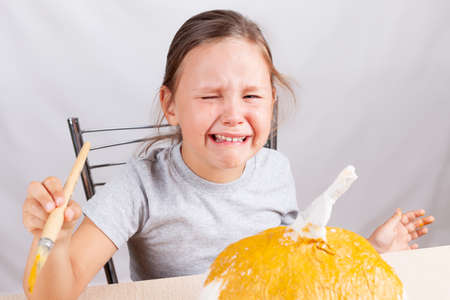 a girl cries and makes a handmade papier-mache pumpkin for Halloween on a gray background,