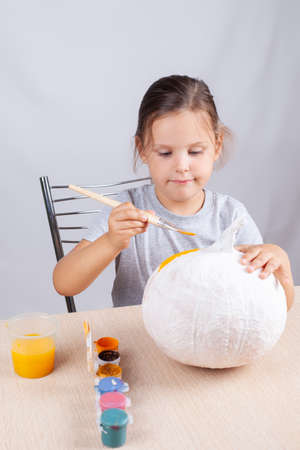homemade decoration for Halloween, a child paints a pumpkin out of paper and napkins, a hobby on self-isolation