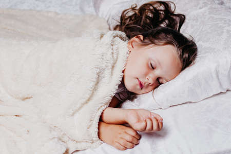 a five-year-old girl sleeps peacefully on an orthopedic pillow, home comfort and warmth, healthy sleep