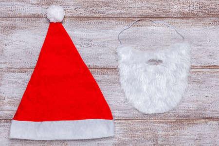 red Santa hat and white fake beard on wooden background 免版税图像