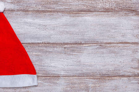 mock up, half red Santa Claus hat on wooden background, Christmas card
