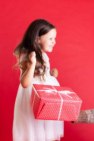 close up a girl in a white dress sideways jumps from happiness when receiving a gift isolated on a vivid background