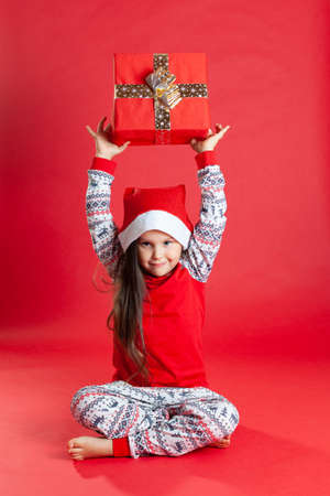 smiling girl in pajamas and a Santa Claus hat, barefoot sitting on the floor holding a present over his head, isolated