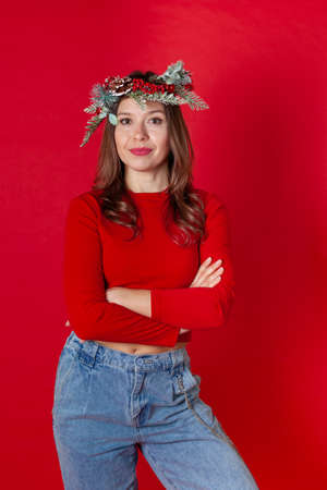 smiling young woman in a Christmas wreath, turtleneck and jeans, with her arms crossed on her chest, on a red background