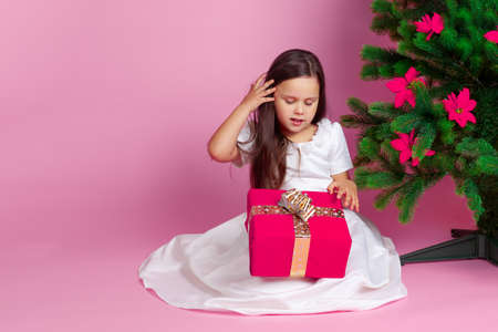 mock up smiling girl with long hair and white dress opens gift box with a bow and adjusts her hair, on a pink background Stock fotó