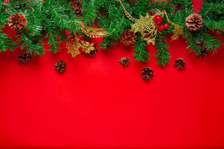 mock up of a Christmas tree garland with cones, Golden decor and red berries, isolated on a scarlet background Stock fotó