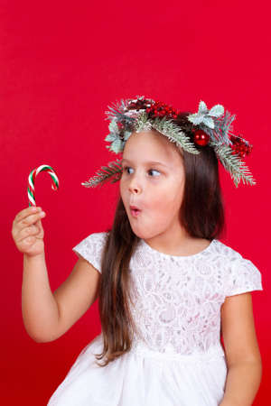 close up of a surprised girl in a Christmas wreath looking at a caramel cane in her hand, on a red background Stock fotó