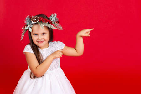 mock-up portrait of a smiling girl in a Christmas wreath, pointing with her index fingers, on a red background