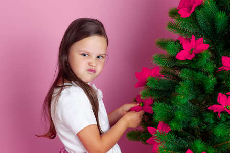 mock up a Moody, offended girl decorates the Christmas tree with mistletoe flowers, on a pink background
