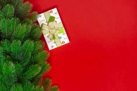 mock up of a Christmas tree and a green gift box on a red background with space for text