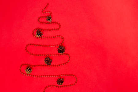 postcard from a garland of beads laid out in the form of a Christmas tree with decorations from cones, isolated on a red background, mock up Stock fotó