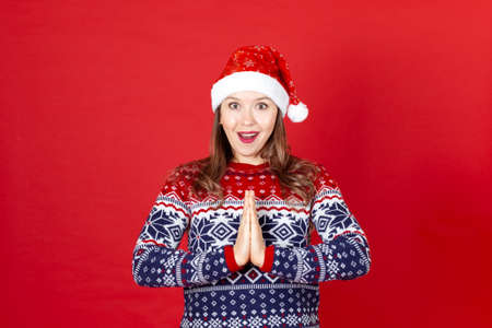 portrait of a young surprised woman with hands in prayer in a Christmas sweater Santa Claus hat on a red background Stock fotó