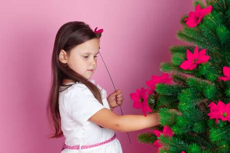 mock up of a girl with long hair and a white dress decorating a Christmas tree with red flowers on a pink background