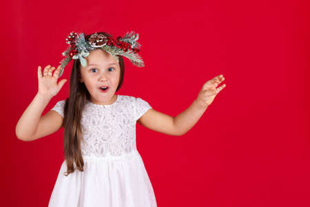 mock up of girl in Christmas wreath and white dress waving her hands in surprise on a red background with space for text Stock fotó