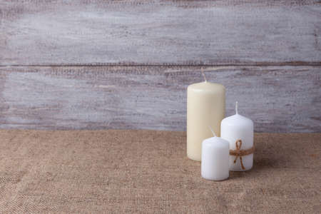 mock up of two white candles in jute rope and a vanilla candle on a wooden background and burlap