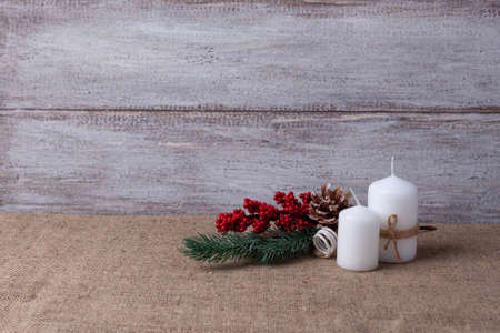postcard of two white candles and a Christmas tree branch on a wooden background and burlap Stock fotó