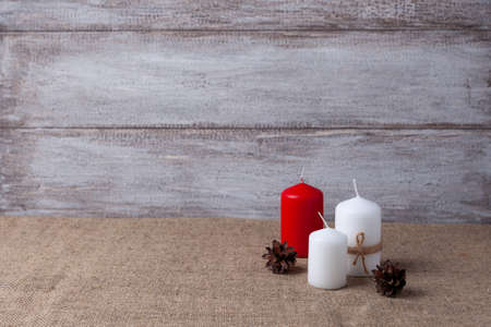 mock up of two white candles in jute rope and a red candle, cones on a wooden background and burlap