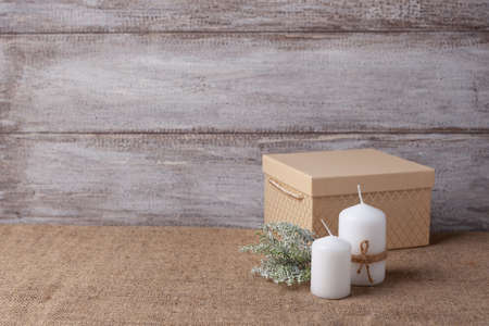 mock up of two white candles in a jute rope and beige gift box, a sprig of lichen yagel on a wooden background Stock fotó