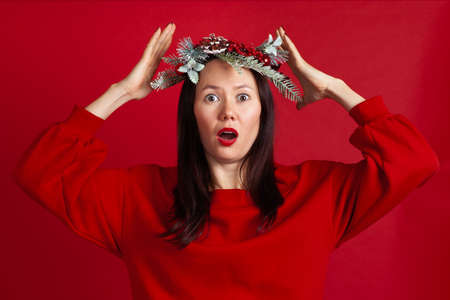 close-up portrait of worried, upset Asian young woman in Christmas wreath with hands holding her head, on red background
