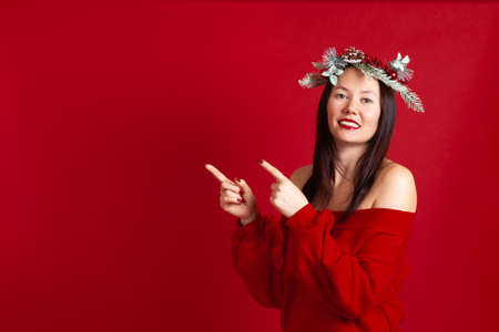 mock up, a smiling Asian young woman, points her index fingers at a free space for text, on a red background