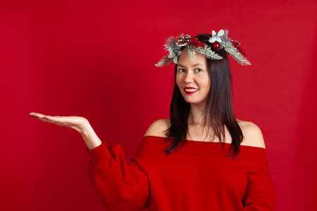 close up of a smiling Asian young woman with an empty space in the palm of her hand for advertising, on a red background Stock fotó