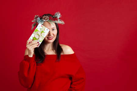close-up portrait of happy Asian young woman in a Christmas wreath hiding one eye behind a gift box, on a red background