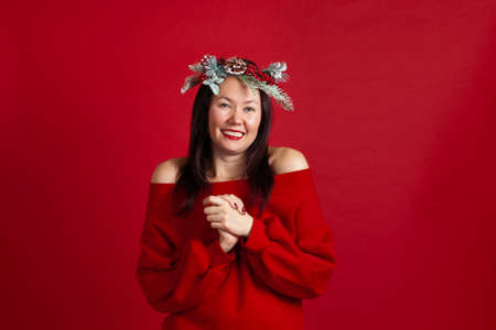 portrait of a happy laughing Asian young woman delighted with shopping or gift, on a red background
