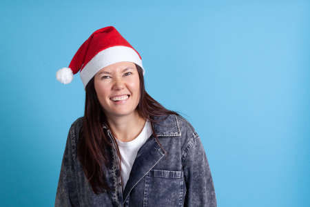 close up portrait of mischievous Asian young woman in Santa hat smiling and biting lip with her teeth on blue background