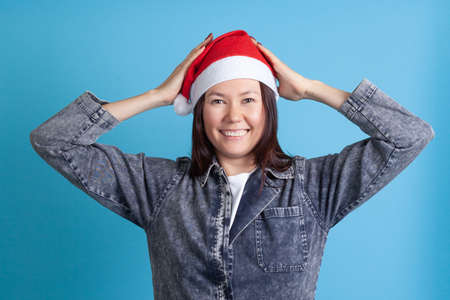 smiling Asian young woman in a Santa hat holds her head with her hands, isolated on a blue background