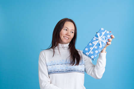 close up portrait of a smiling Asian young woman in a sweater looking at a blue gift box isolated on an azure background