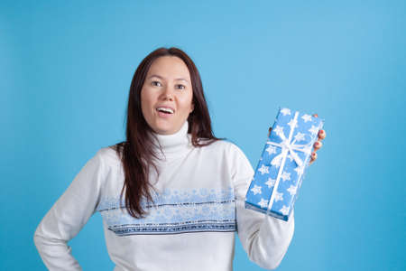 close-up portrait of surprised happy Asian young woman in sweater receiving Christmas gift, isolated on azure background Stock fotó